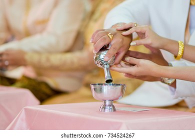 to pour water slowly onto the ground .so that the dead might benefit from meritmaking.thai wedding