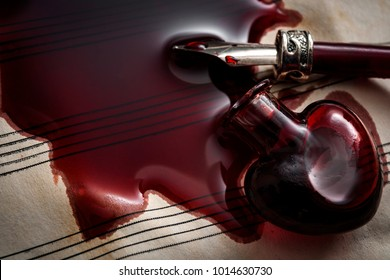 To pour your heart out through art or catarsis concept with an aged music paper with spilled blood coming from a glass heart and a vintage quill pen soaked in blood with copy space