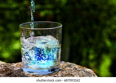 Poured clean drinking water in a glass on nature background. Copy space