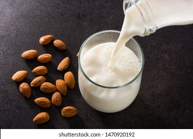 Pouring almond milk in glass on black background