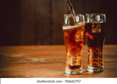 Pouring beautiful cold drink of Cola with ice cubes with a boiler straws in glasses on wooden background with free space.