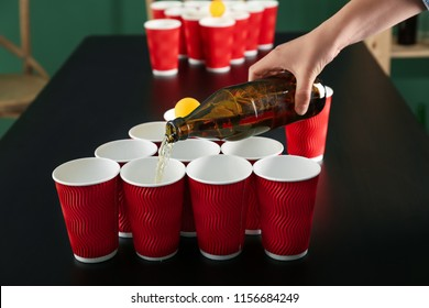 Pouring of beer from glass bottle into plastic cups on table. Beer pong game