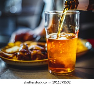pouring beer in glass from bottle on bar or pub