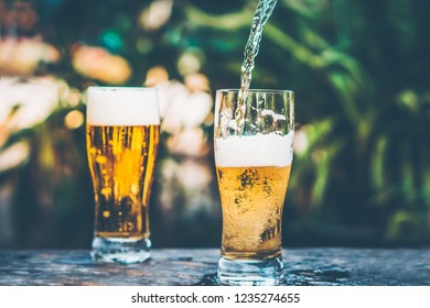 pouring beer to a glass close up in vintage tone background