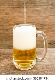 pouring beer in the glass on a wooden background
