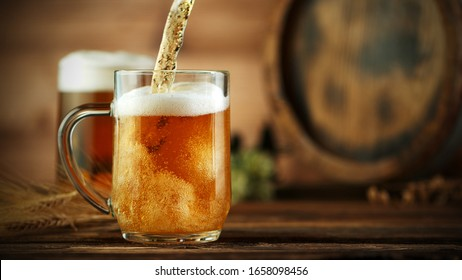 Pouring beer into glass pint, placed on wooden table with keg.