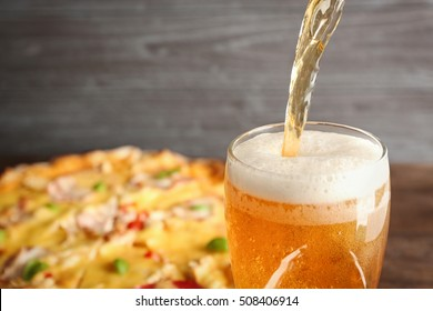 Pouring beer on pizza background