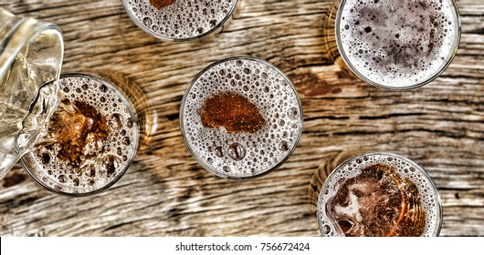 Pouring beer.glasses with beer stand on a wooden table.Closeup. View from above.