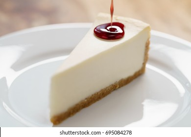 pouring berry jam on slice of traditional new york cheesecake on white plate on wood table