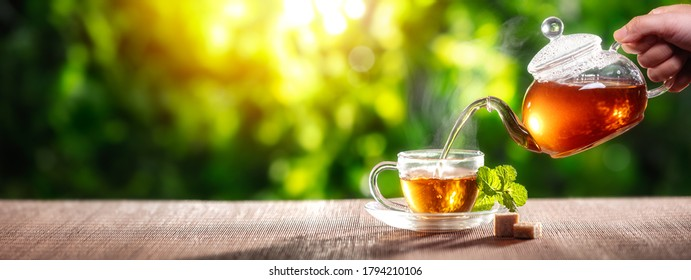 Pouring black tea into glass cup on wooden table - Shutterstock ID 1794210106