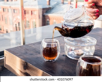 Pouring black tea in a transparent glass, city on a background, female hand holding a transparent teapot