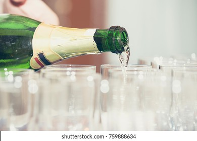 Pouring from bottle to New Year's champagne glasses