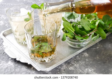 Pouring bourbon into a glass, process of making mint julep.Closeup of an old-fashioned glass with mint and crushed ice on the silver vintage tray