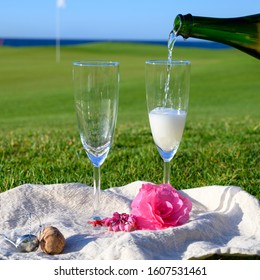 Pouring of bubbles white champagne or cava wine in two glasses during romantic event or celebration on green golf club grass with sea view