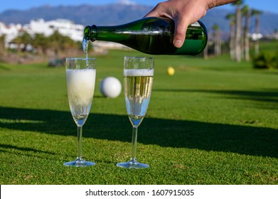 Pouring of bubbles white champagne or cava wine during golf competition event or celebration on green golf club grass with mountains view in sunny day