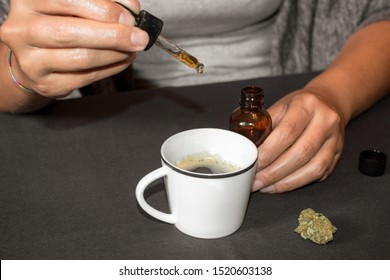 Pouring CBD tincture in a coffee cup, natural medicine made with marihuana. Woman using cannabis oil with a dropper in a table with marihuana bud.