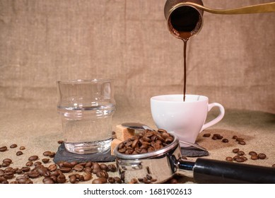 Pouring cezve or turkish coffee into a cup of coffee. Delicious strong coffee.