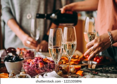Pouring champagne at a dinner party with friends. Dinner table, celebrating Christmas or New Year eve.