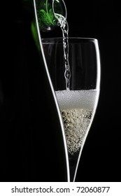 pouring champagne in glass on black background