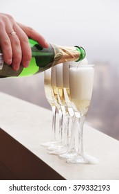 Pouring champagne into glasses at a height