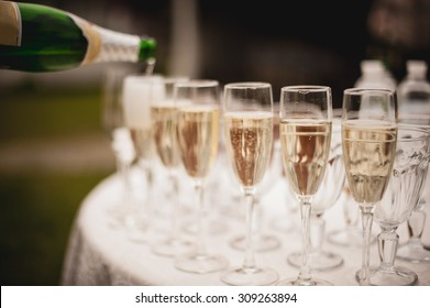 Pouring champagne into a glasses standing on table