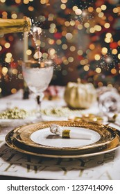 "Pouring champagne on a luxury golden glass, New year and christmas table setting with exclusive and luxury golden cutlery, over a tabletop with celebrations world "" new year"""