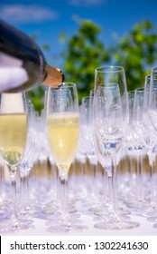 Pouring champagne, sparkling wine into glasses at wedding reception, party outdoors, copy space