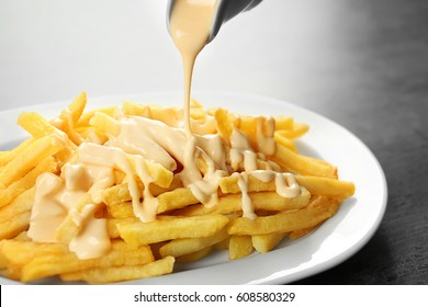 Pouring cheese sauce on french fries, closeup
