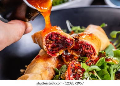 Pouring chilli sauce onto plate of spring Rolls