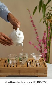 Pouring chinese green tea into glass teapot