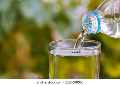 Pouring of clear drink water from bottle into the glass on blurred green nature background with copy space for text.