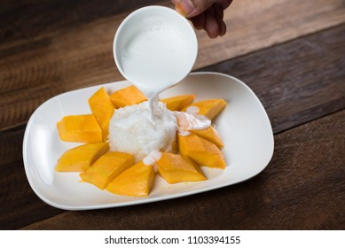 pouring cocunut milk onto mango sticky rice, a traditional thailand dessert. food and gastronomy concept