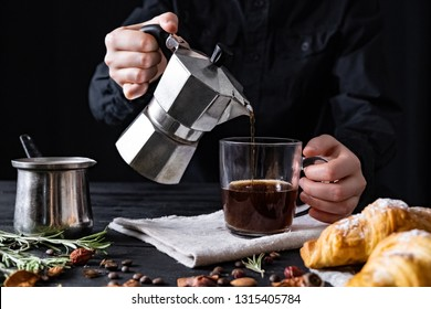 Pouring coffee from an italian percolator, shot in low key. Male hands pour black coffee from italian moka brewer