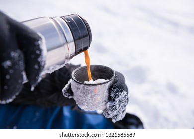 Pouring the coffee from the thermos outdoors. Snowy mountain background. Winter holidays, tourism, travel and people concept
