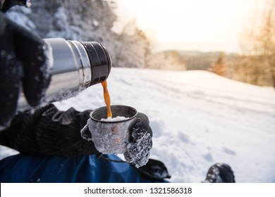 Pouring coffee from the thermos outdoors. Snowy mountain background. Winter holidays, tourism, travel and people concept