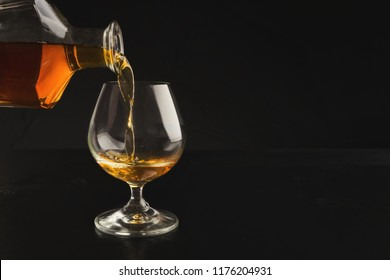 Pouring cognac from bottle into glass on black background, copy space. Degustation of elite alcohol