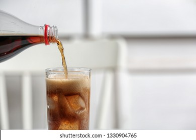 Pouring cola from bottle into glass on blurred background, closeup. Space for text
