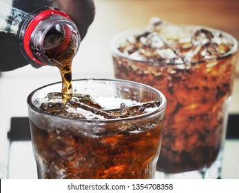 Pouring cola drink on glass