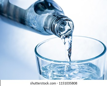 Pouring of cold clear drink water from bottle into glass, close up, blue toned on white background