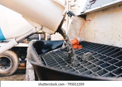 pouring concrete from a concrete mixer to the pump - pouring concrete slab
