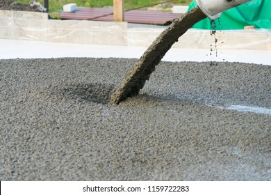 Pouring concrete from a concrete mixer. The work of people pouring concrete.