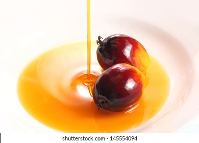 Pouring cooking oil on white background with oil palm fruits