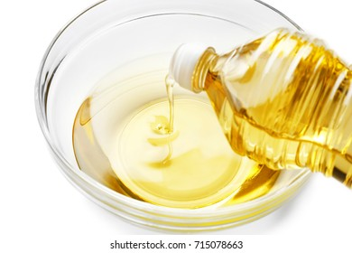 Pouring cooking oil from plastic bottle into glass bowl, on white background