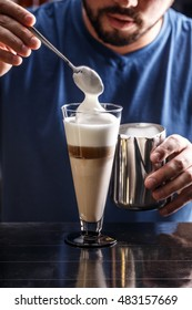 Pouring cream into a coffee latte