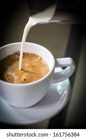 Pouring cream into a cup of coffee