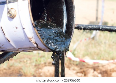 pouring crude oil from bucket. waste management