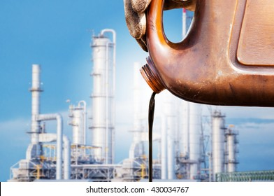 pouring crude oil from sample canned oil Refinery distillation towers background. crude oil low price concept.