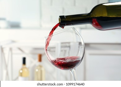 Pouring delicious red wine into glass on light background