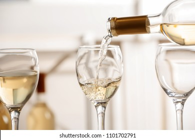Pouring delicious white wine into glass on light background
