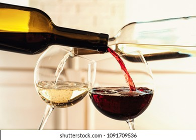 Pouring delicious wine into glasses on light background